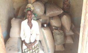 VSLA beneficiary sitting at the entrance of her grain store